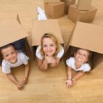 Immagine con mamma e due bambini dentro box di cartone
