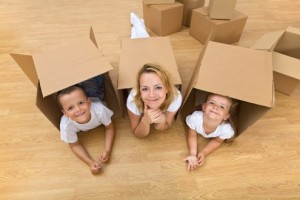 Family in a new home with cardboard boxes - having fun on the floor